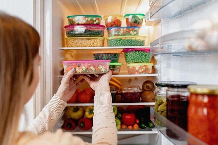 Woman Putting Food In Fridge