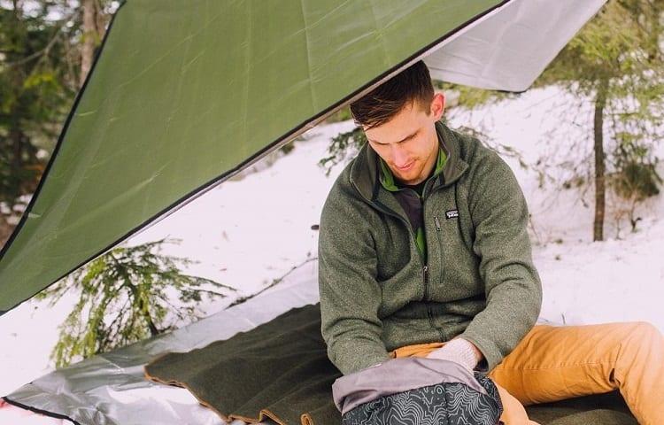 man sitting on survival blanket